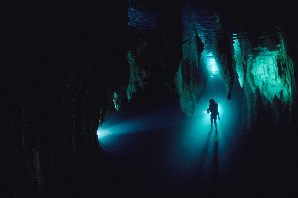 In Taucher wird in der Chandelier Cave in Palau von Scheinwerfern angestrahlt. Höhlentauchen kann gefährlich sein, ...