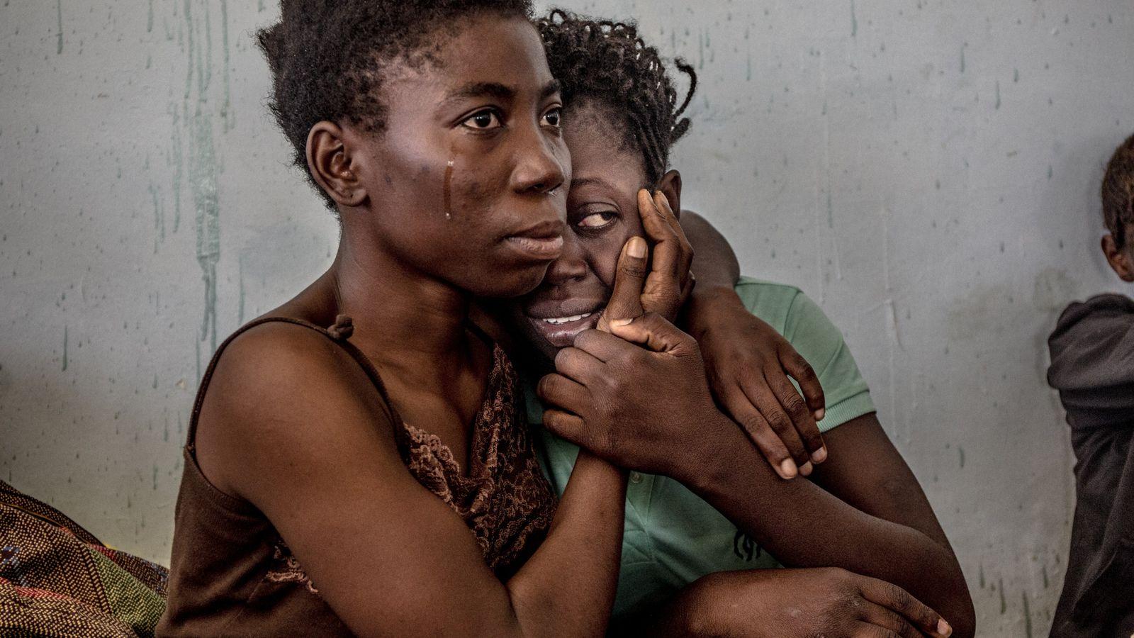 Nigerianische Migranten weinen und umarmen sich im August 2016 in einem Auffanglager für Flüchtlinge und Migranten ...