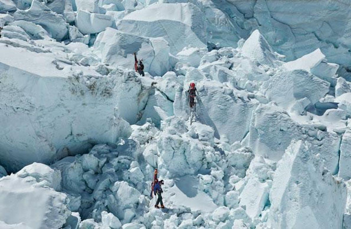 Drei Kletterer steigen über den Khumbu-Eisbruch ab, nachdem sie zur Gewöhnung an die Höhe einige Zeit …