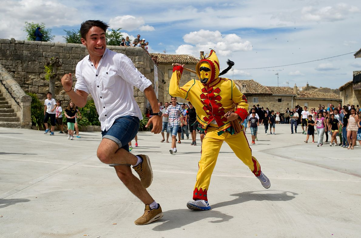Ein kostümierter Teufel jagt einen Zuschauer