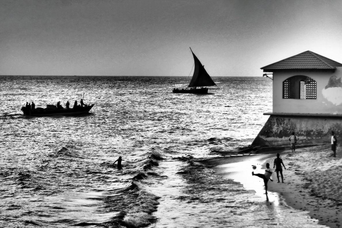 An einem Strand in Stone Town auf Sansibar genießen die Menschen beim Schwimmen, Bootfahren und Fußballspielen ...