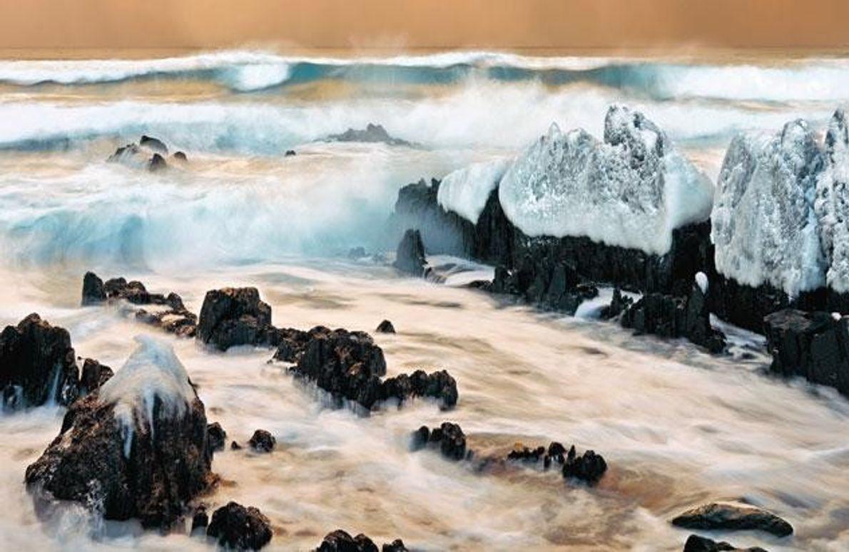 Kupferfarbene Schneewolken über einer eisigen Brandung machen die Varanger-Halbinsel zu einer Landschaft wie von einer anderen …