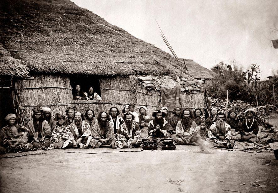 Eine Gruppe von Ainu – der indigenen Bevölkerung Japans – posiert in den 1880ern für ein ...
