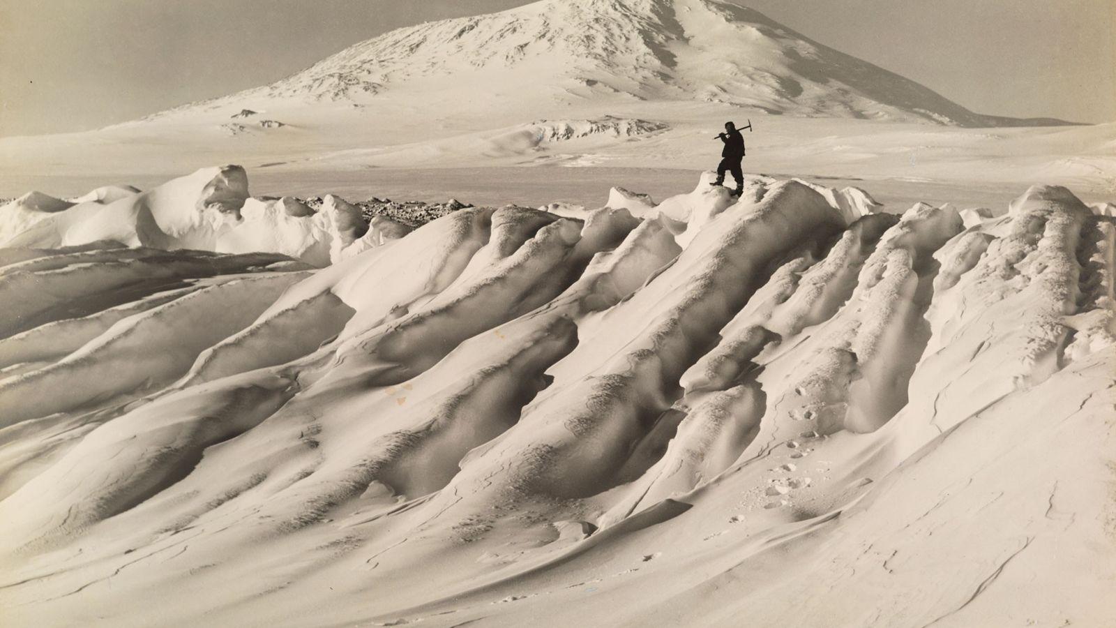 Ein Mitglied von Robert Falcon Scotts Terra-Nova-Expedition zum Südpol steht auf einem vom Wasser zerfressenen Eisberg ...