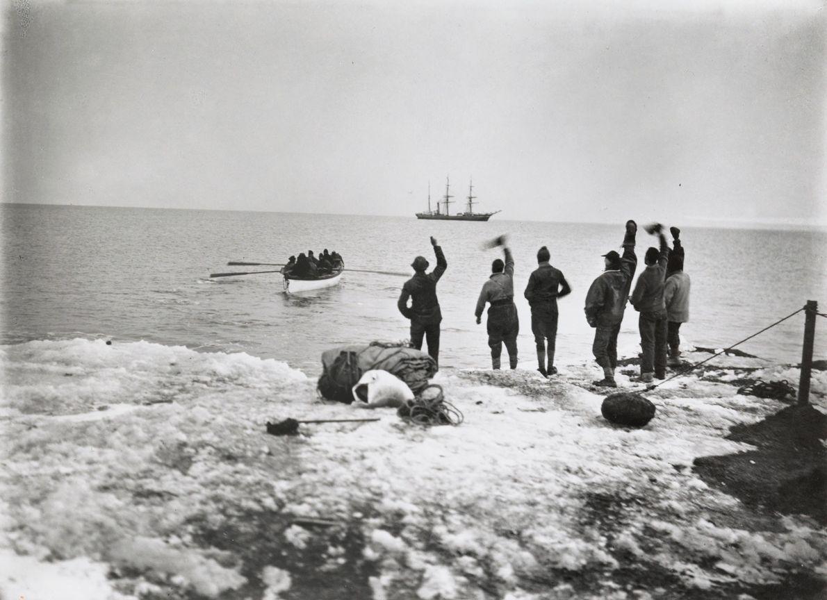 Mitglieder der Polarexpedition von Robert Falcon Scott stehen am Ufer und winken ihren abreisenden Kameraden zu. ...