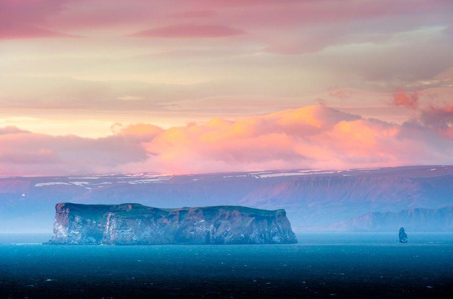 Pastellfarbene Wolken ziehen über die Insel Drangey hinweg.