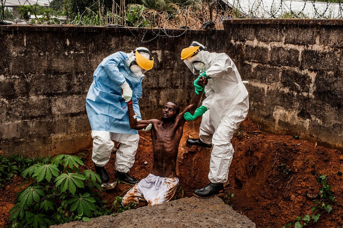 Zwei Pfleger des Hastings Ebola Treatment Center in Sierra Leone bringen einen mit Ebola infizierten Mann …