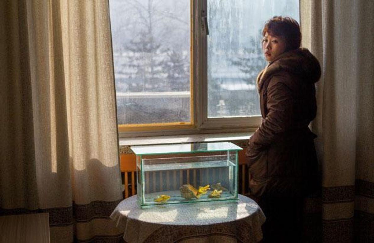 Die Frau steht im Mantel am Fenster und wärmt sich am Morgenlicht.