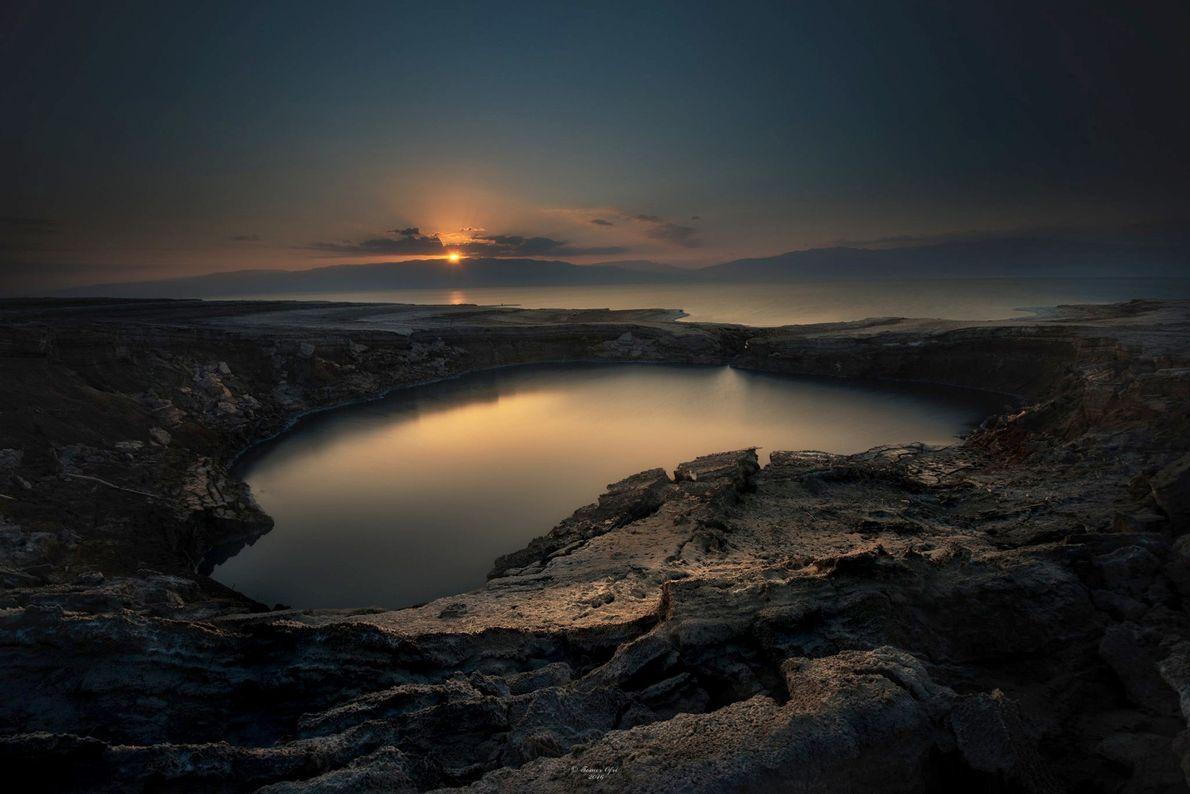 Die Morgensonne hängt zwischen den Wolken über einem Krater am Rande des Toten Meers im Ein ...
