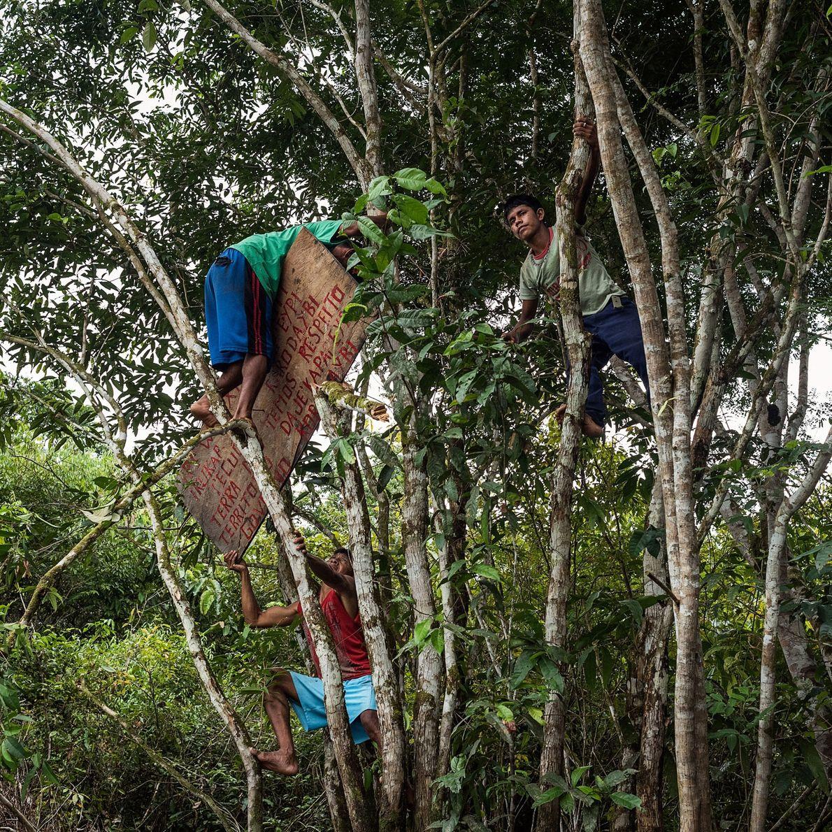 Munduruku-Krieger hängen ein Schild auf