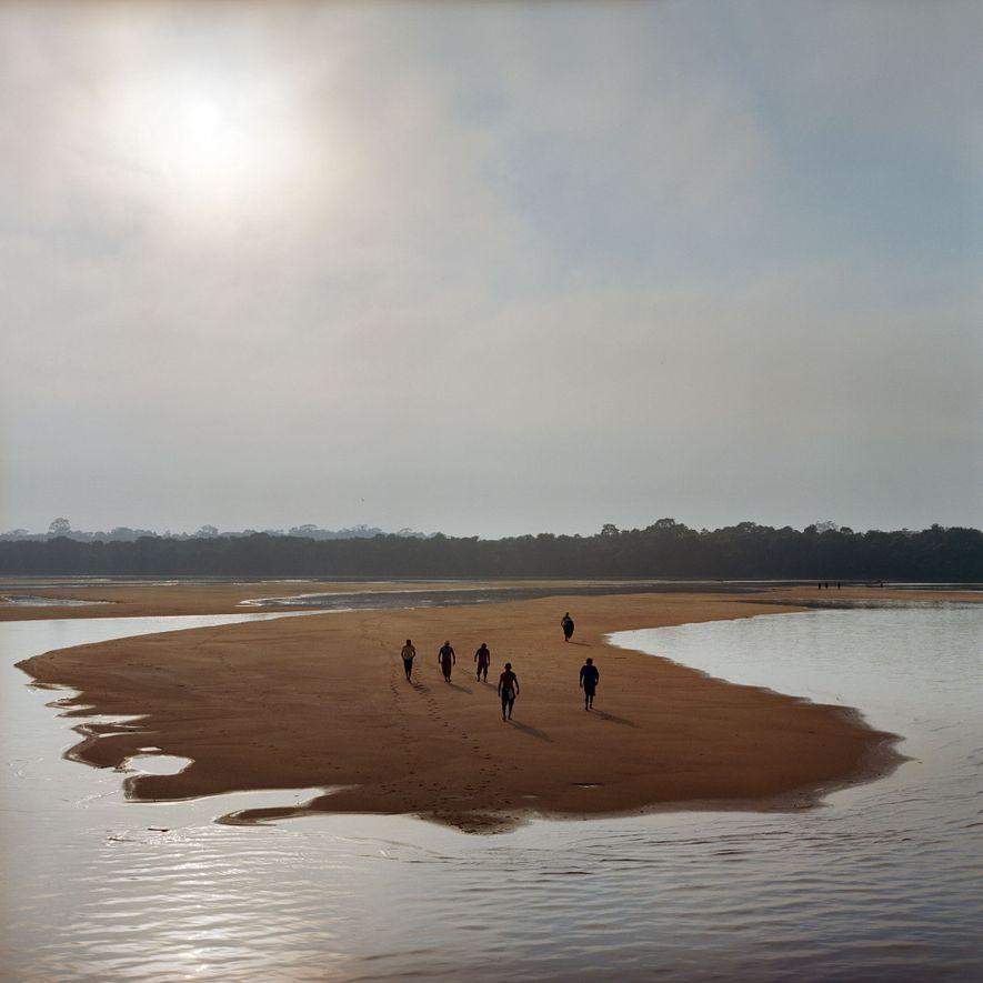2014. Munduruku laufen auf einer Sandbank des Tapajos und bereiten sich auf einen Protest vor. Nach Jahren des Kampfes konnten die Munduruku die Regierung dazu bewegen, ihr traditionelles Gebiet offiziell anzuerkennen. Diese Anerkennung verhinderte, dass das brasilianische Umweltministerium die Umweltgenehmigung für das Tapajos-Wasserkraftwerk (12.000 Megawatt) erteilen konnte. Der Kampf geht jedoch weiter, da 40 weitere Staudämme im Flussbecken nach wie vor in Planung sind.