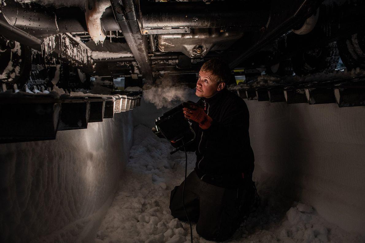 Vor der Neumayer-Station untersucht Nils Peters in einem selbstgeschaufelten Graben die Unterseite eines Trucks.