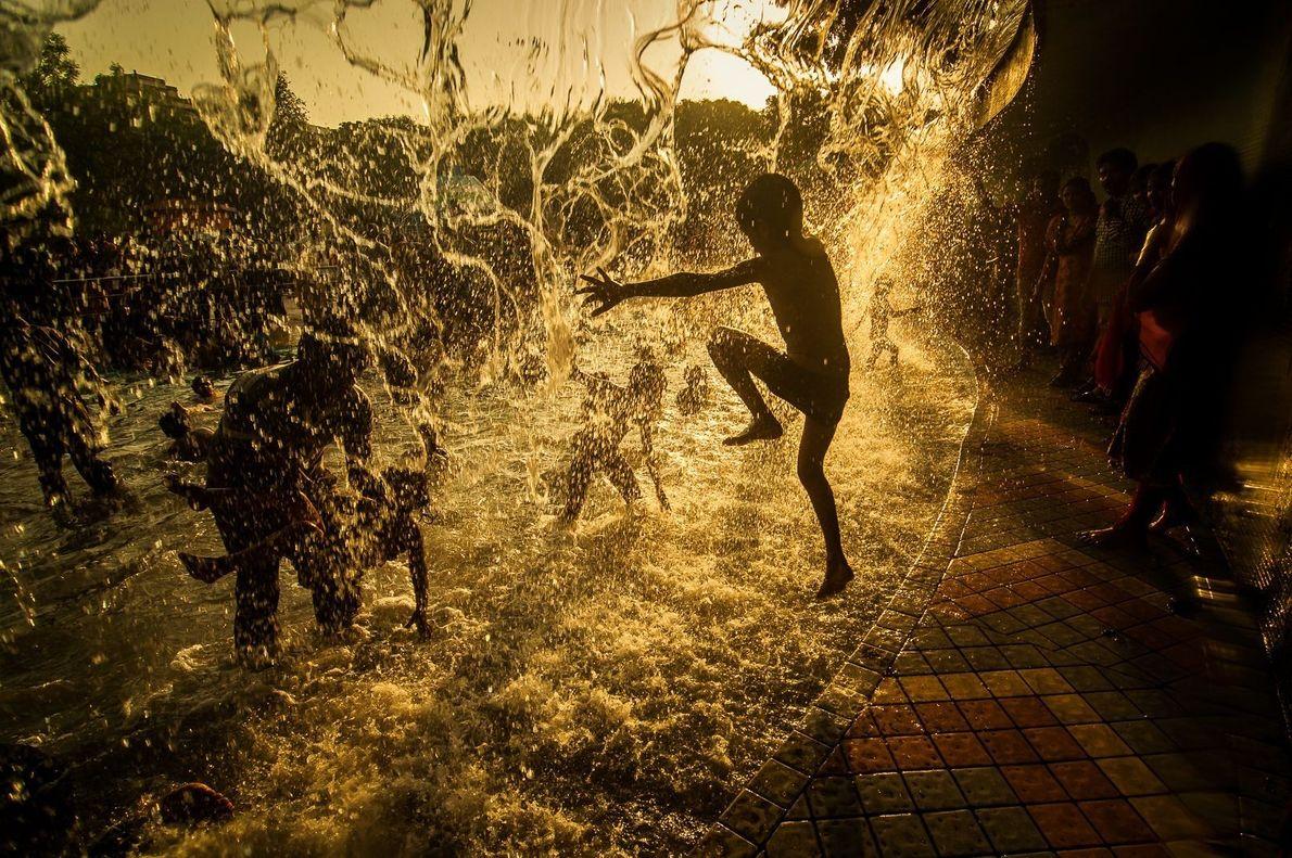 Kinder spielen im indischen Hyderabad in einem Springbrunnen
