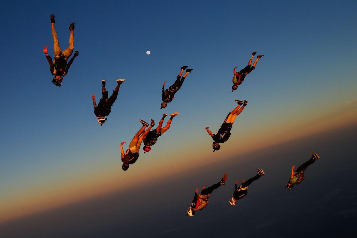 Bei Sonnenuntergang nähern sich Skydiver über dem US-Bundesstaat Texas im freien Fall dem Boden, ehe sie ...