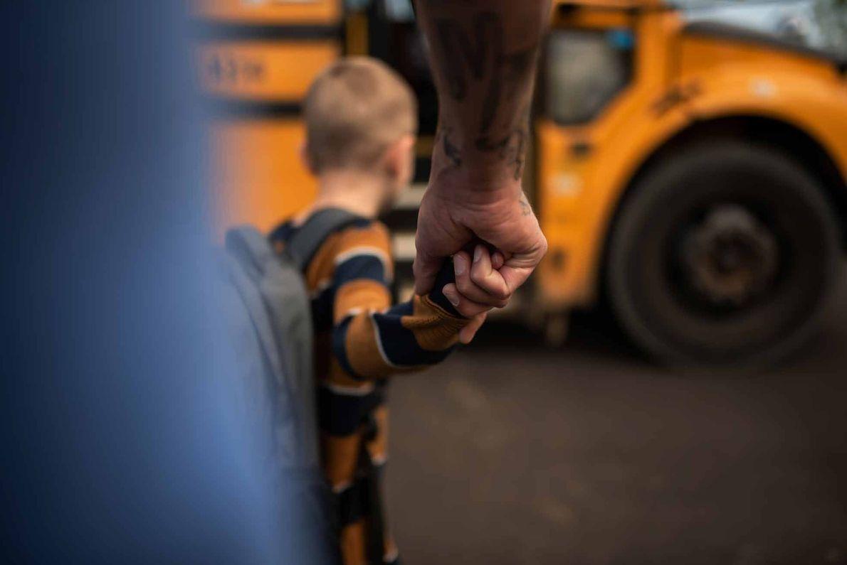 Vater und Sohn vor dem Schulbus