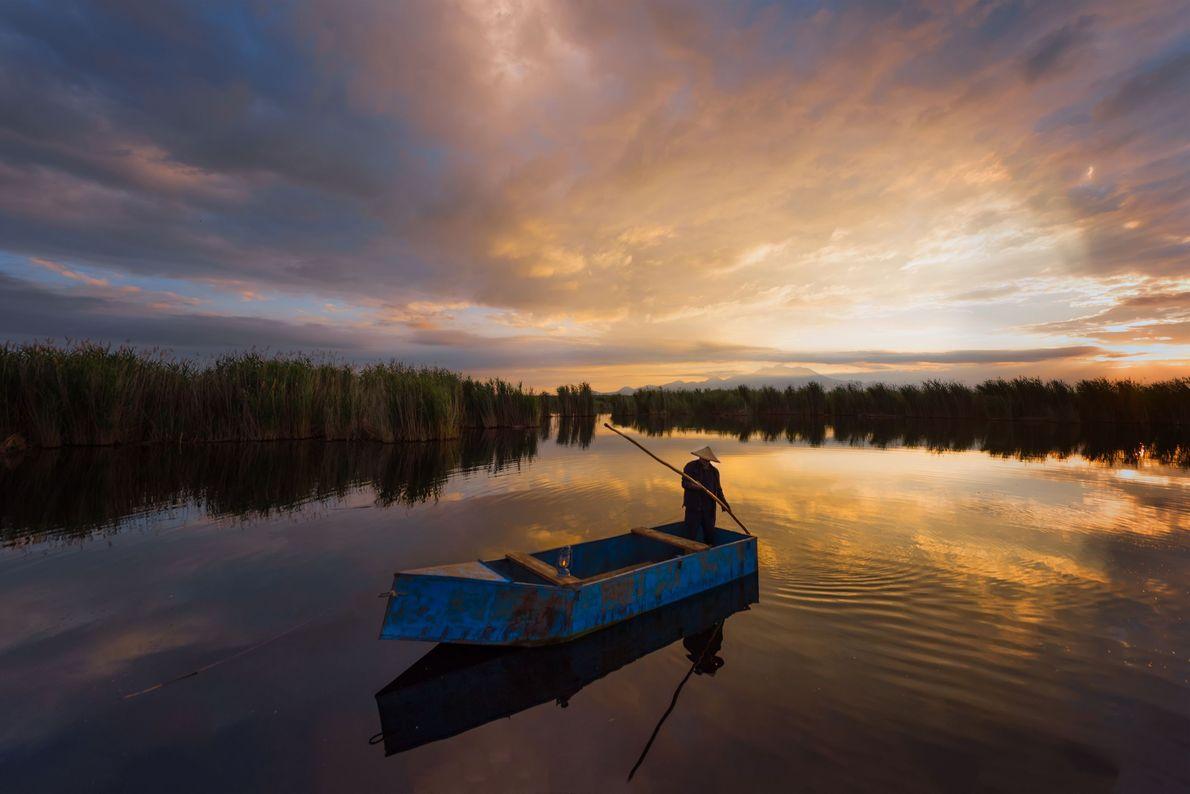 Ein Fischer lenkt sein Boot durch einen ruhigen See in der türkischen Stadt Keyseri.