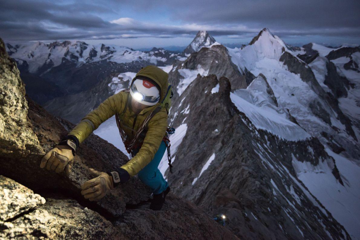 Eine Kletterin sucht Halt an einer Felsspalte des Zinalrothorn in den Walliser Alpen.