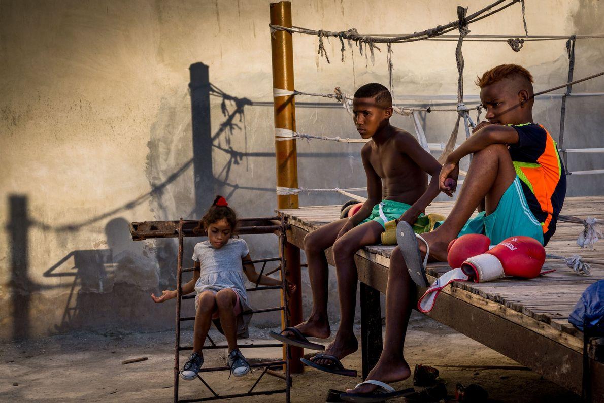 Zwei Jungs sitzen am Rande eines Boxrings in Havanna