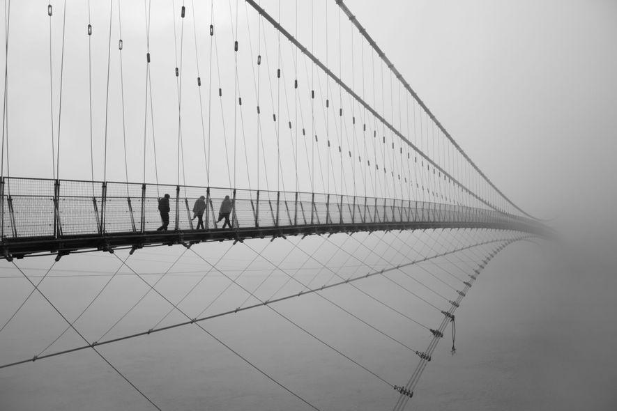 An einem kalten Januarmorgen im indischen Rishikesh überqueren Menschen auf dem Weg zur Arbeit die Lakshman-Jhula-Brücke. ...