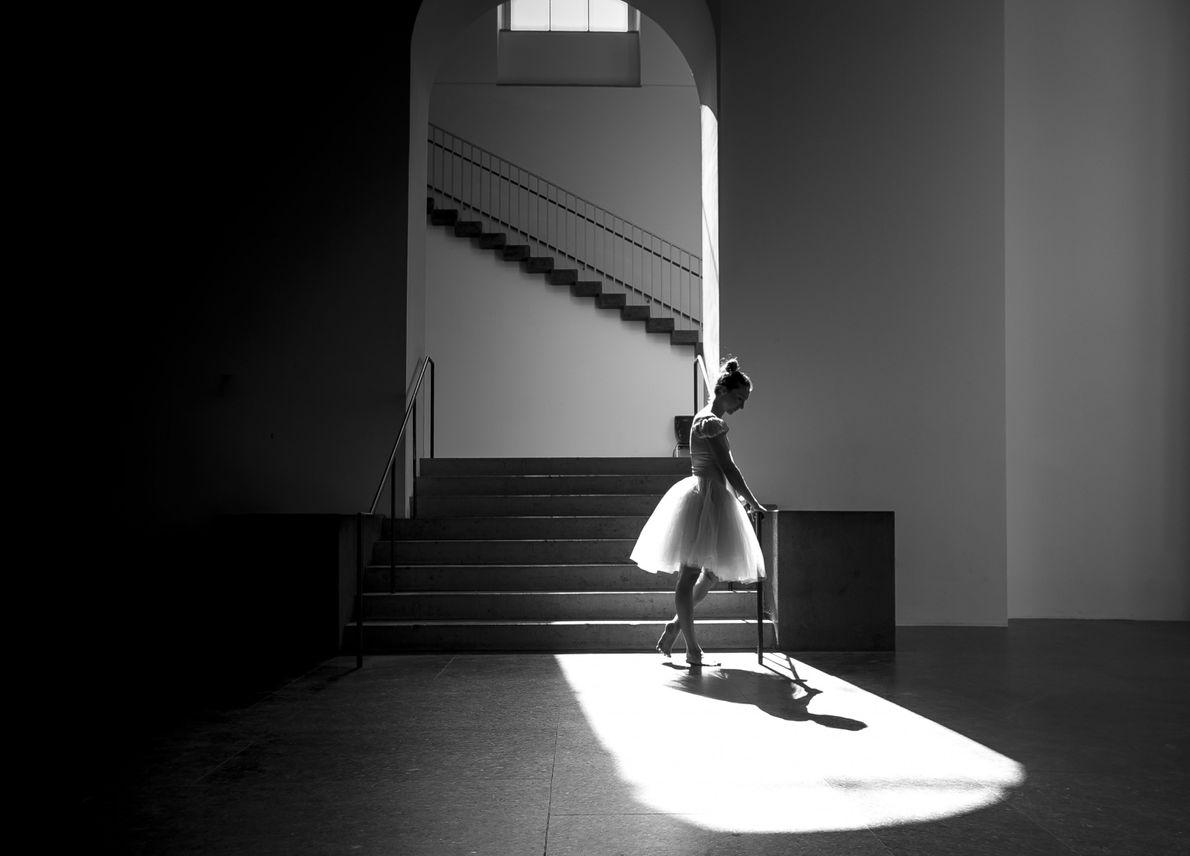 An der Akademie der Bildenden Künste München genießt eine Ballerina einen ruhigen Moment.