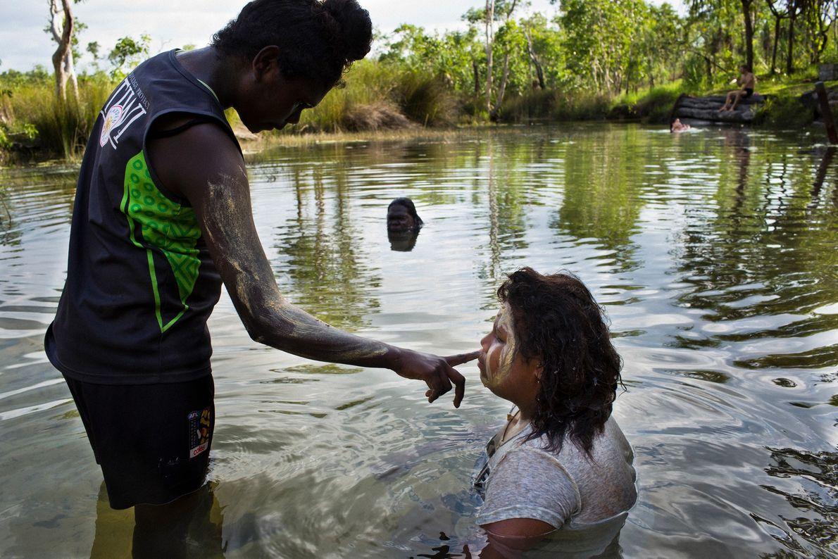 Mädchen bemalen ihre Gesichter mit Lehm aus einem Flussbett. Der Platz ist bei den Inselbewohnern ein ...