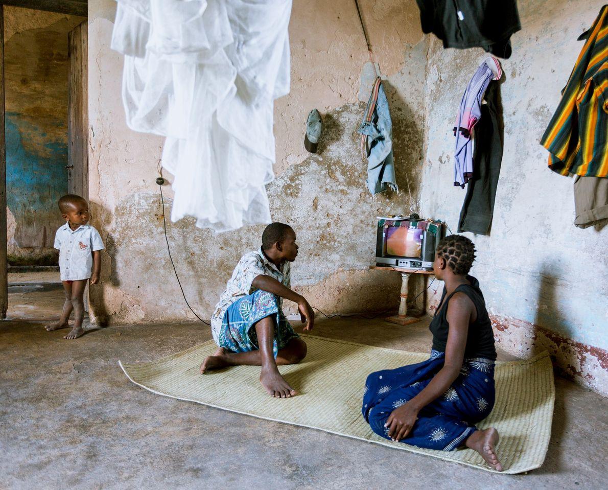 Eine Familie sieht in ihrem Zuhause in einem alten Kolonialgebäude fern.