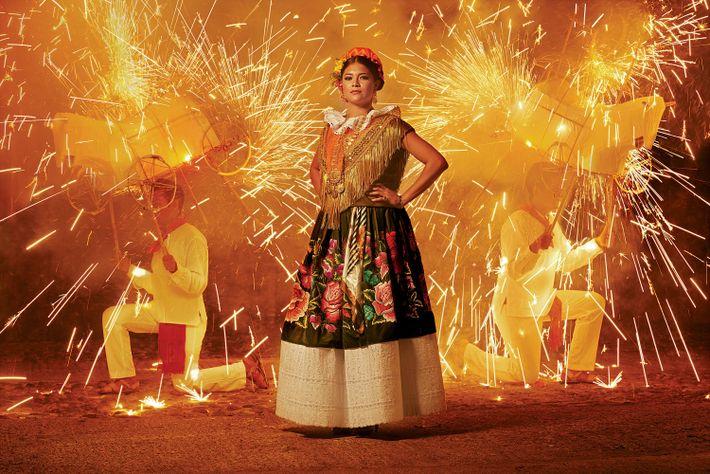 Eine Frau trägt ein traditionelles Tehuana-Gewand. Die Blumen werden mit Seidenfaden auf Samt gestickt und mit ...
