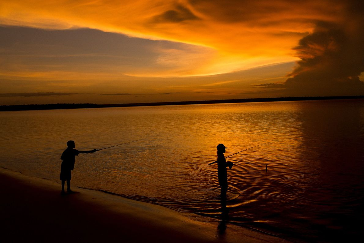 Jungs angeln an der Küste von Melville Island, während sich am Horizont ein Sturm zusammenbraut.
