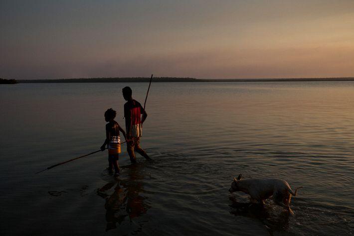 Junge Jäger durchkämmen die Gewässer vor Pirlangimpi auf Melville Island. Mit Speeren jagen sie nach Fischen ...