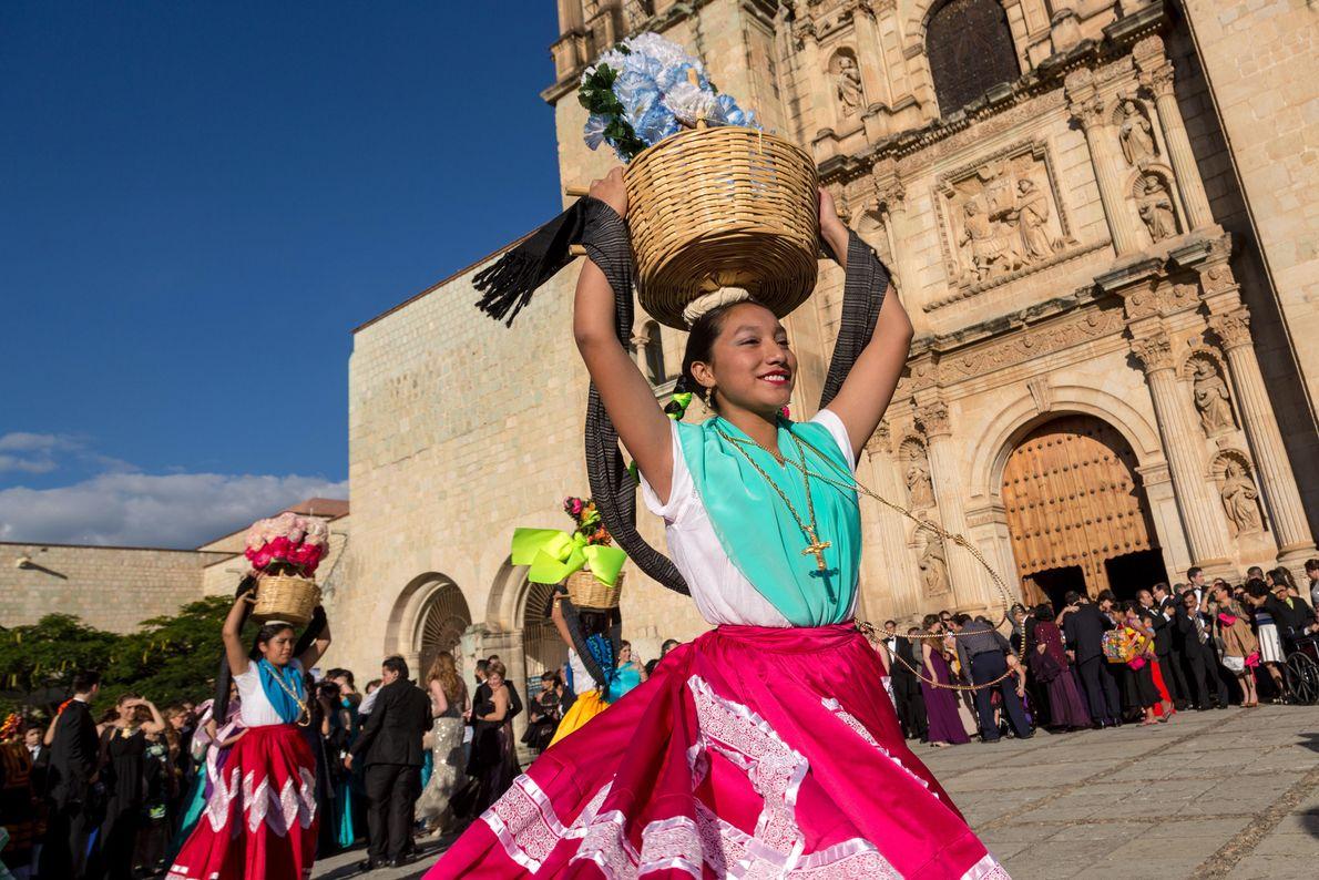 Tänzer in traditionellen Kostümen treten vor der Kirche Santo Domingo im mexikanischen Oaxaca auf.
