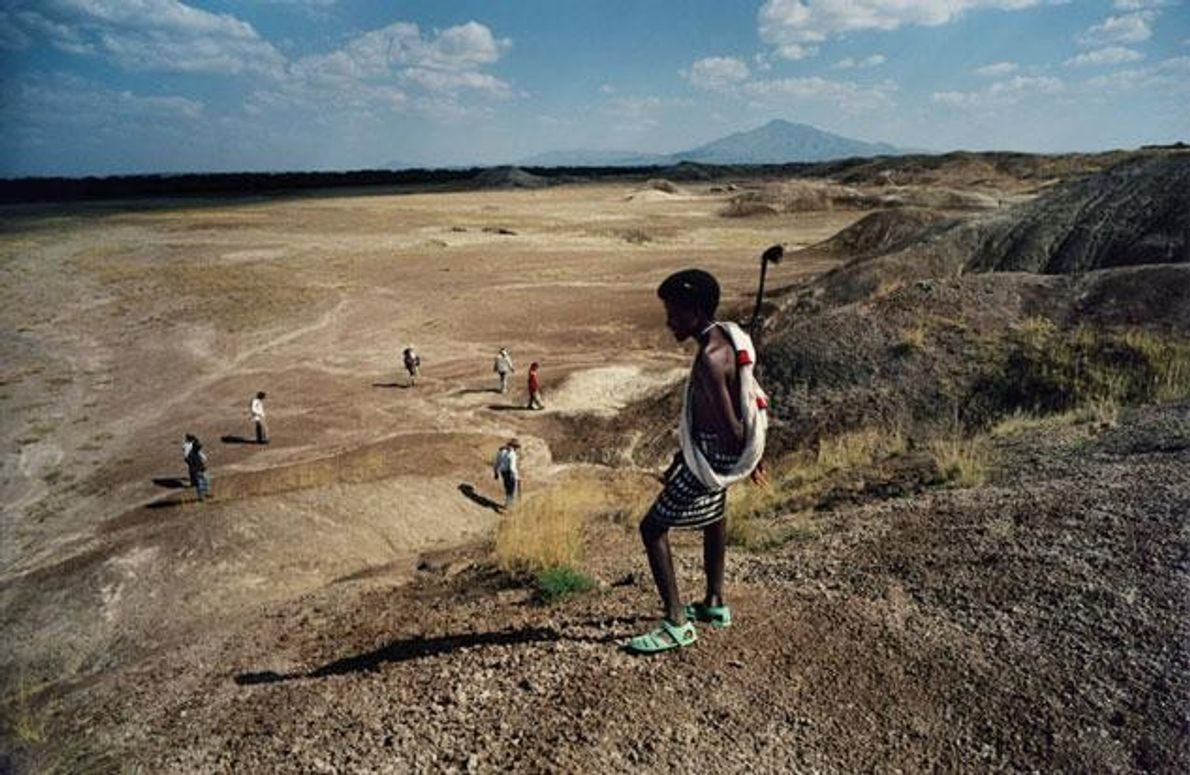 Ein Mann vom Stamm der Afar beobachtet ein internationales Forscherteam bei der geduldigen Suche nach Fossilien …