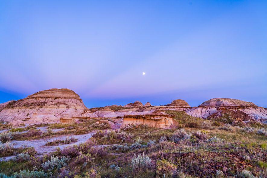 Ein Dreiviertelmond und Sonnenstrahlen über dem Dinosaur Provincial Park in Alberta, Kanada.