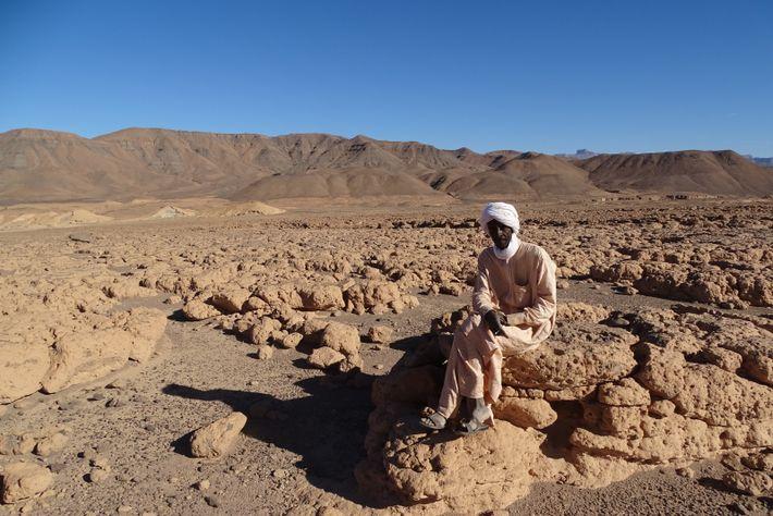 Südlich von Bardai rastet ein Einwohner des Tibesti inmitten von Sandsteinfelsen. Im Hintergrund die an vielen ...