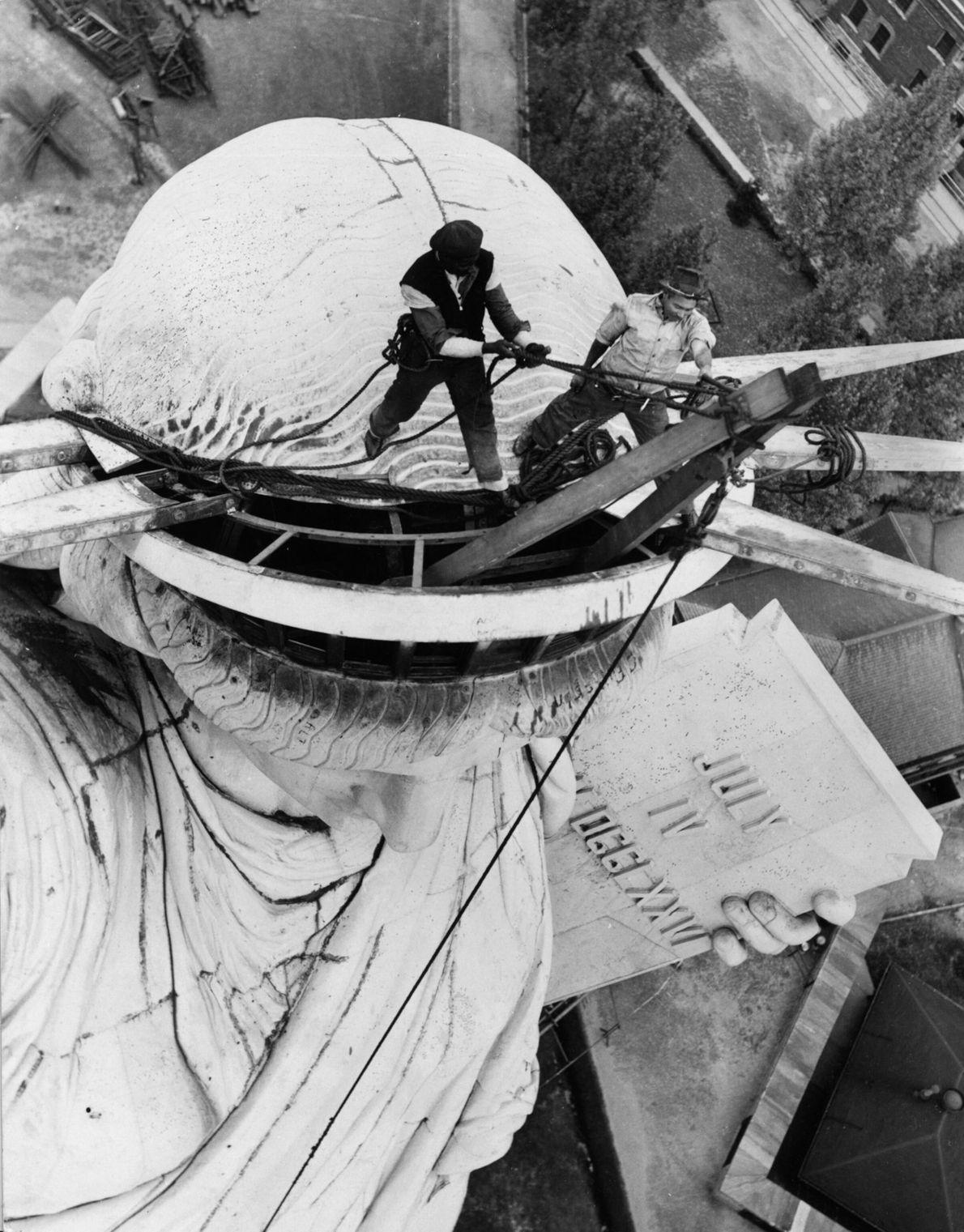 Turmarbeiter entfernen im September 1938 für Renovierungszwecke in Vorbereitung auf die Weltausstellung die Zacken aus der ...