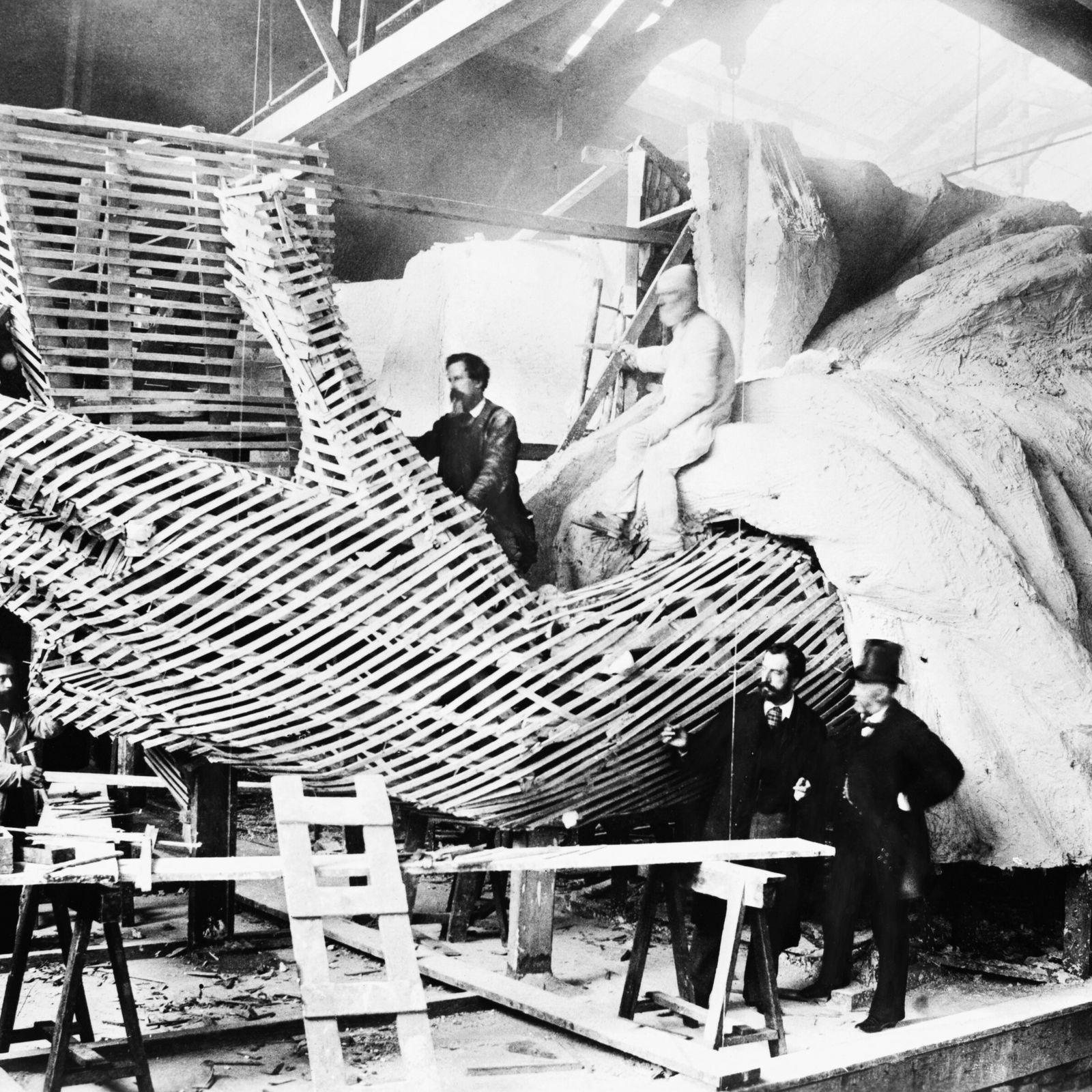 Frédéric-Auguste Bartholdi (Mitte rechts), der die Freiheitsstatue entworfen hat, erklärt einem Besucher die Unterkonstruktion der Hand ...