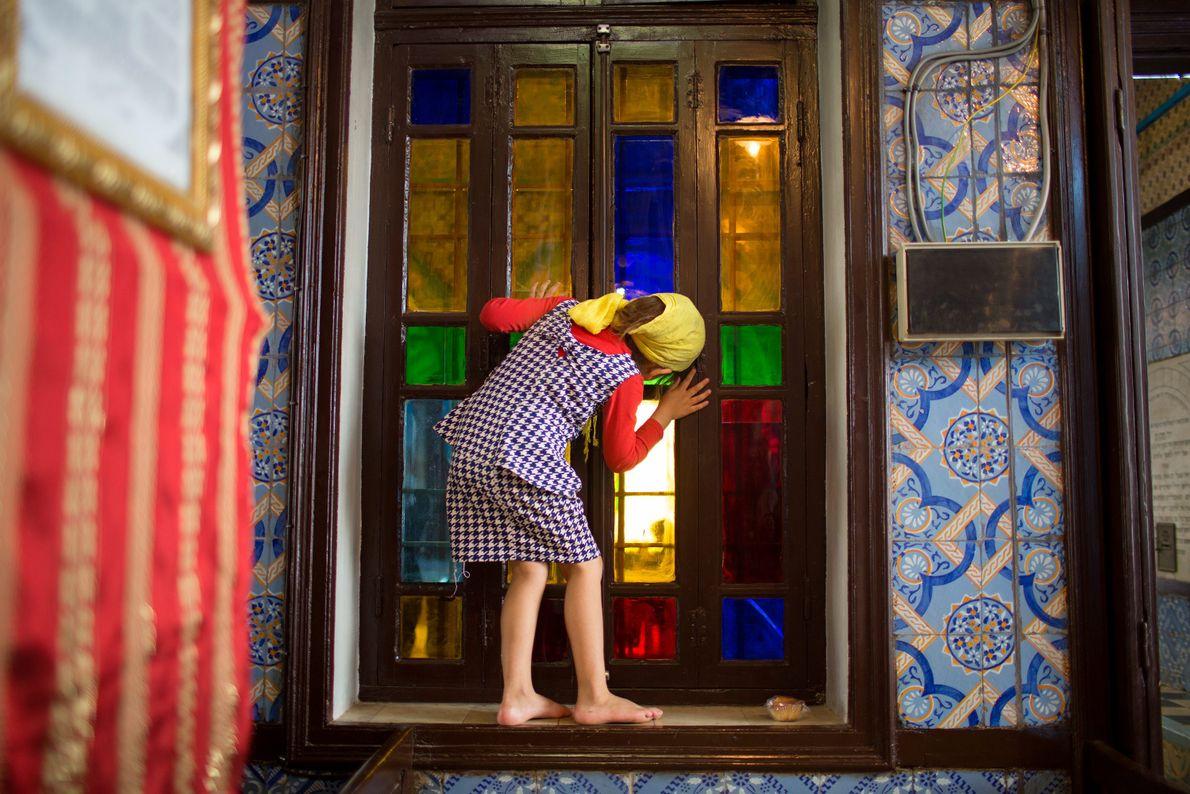 Mädchen schaut durch Fenster