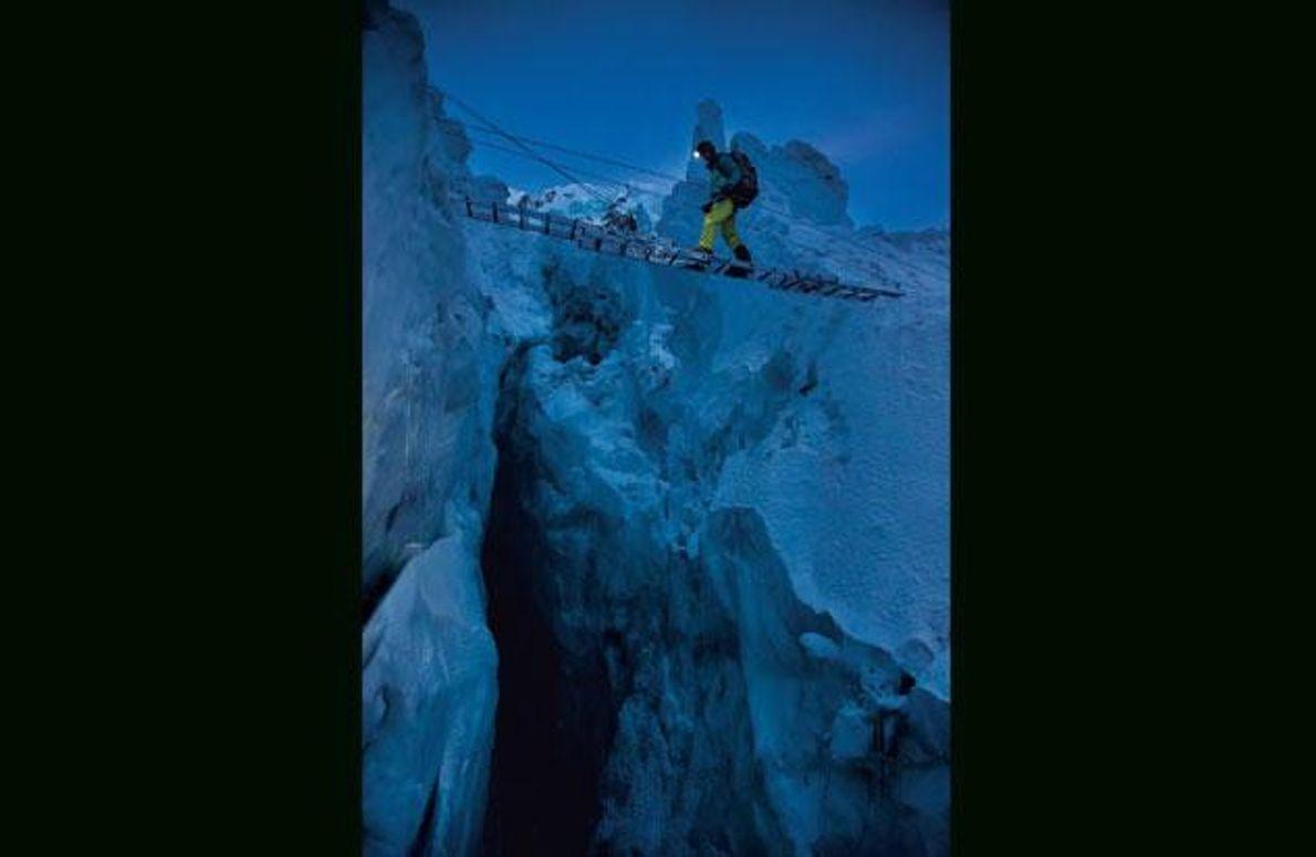 Auf einer Behelfsbrücke aus Leitern überquert Hilaree O'Neill vom NATIONAL GEOGRAPHIC-Team eine Gletscherspalte im Khumbu-Eisbruch. Diese …