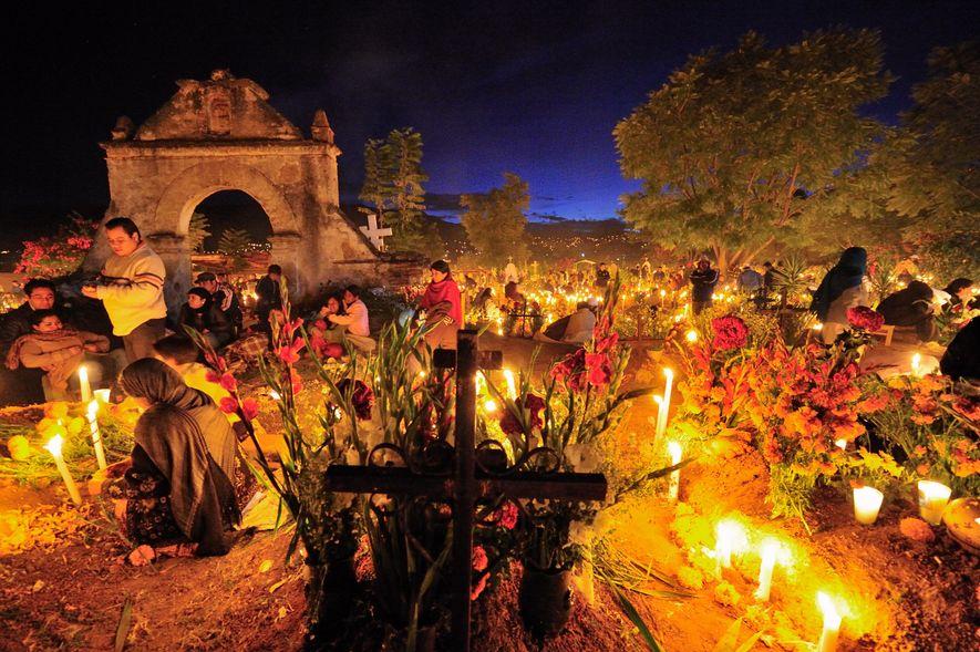 Blumen und Kerzen prägen bei einer Nachtwache am Día de Muertos die Stimmung auf einem Friedhof ...