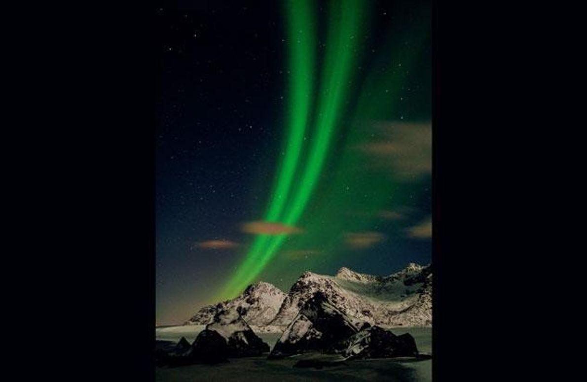 Grüne Nordlichter zucken durch den von Sternen übersäten Himmel über der Lofoten-Insel Flakstadøy.