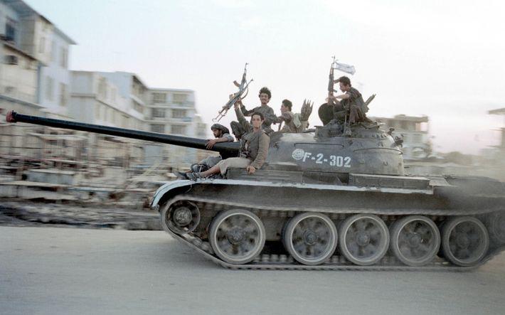 Kämpfer der Taliban fahren 1997 mit einem sowjetischen Panzer durch die afghanische Stadt Masar-e Scharif.