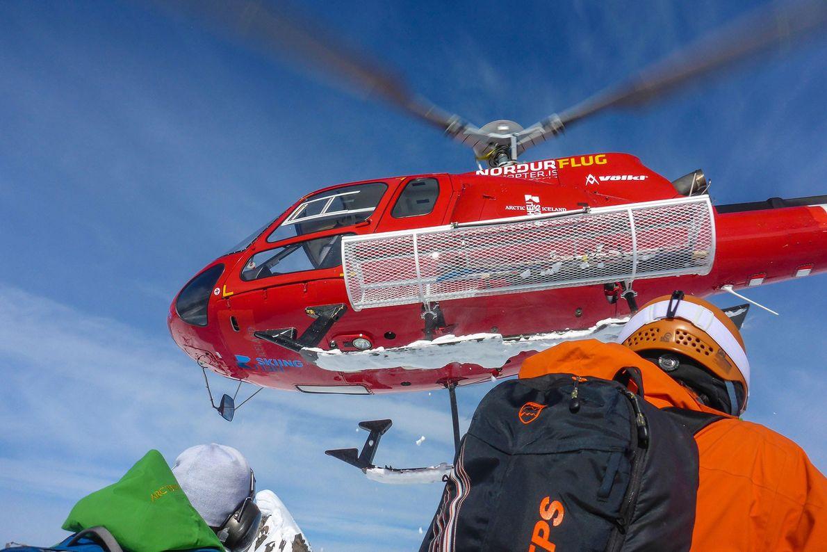 Ein Hubschrauber fliegt weg, nachdem er Heliskifahrer auf der Troll-Halbinsel in Island abgesetzt hat.
