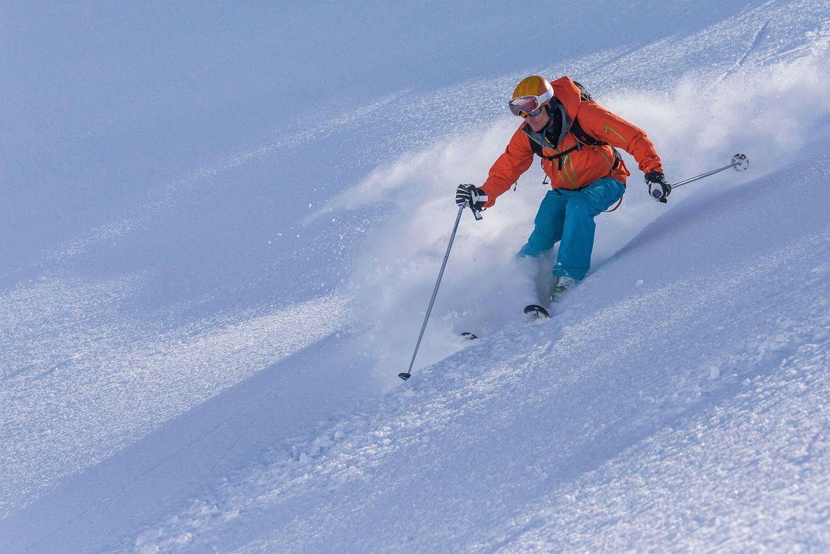 Schnee fliegt von einem Skifahrer auf der Troll-Halbinsel in Island.