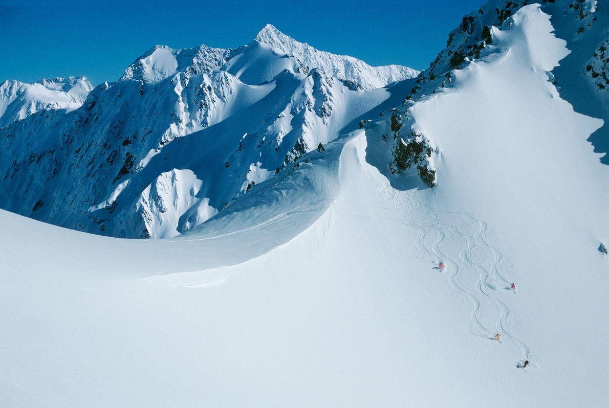 Heliskifahrer winken von der Rakaia Range in den südlichen Alpen Neuseelands.