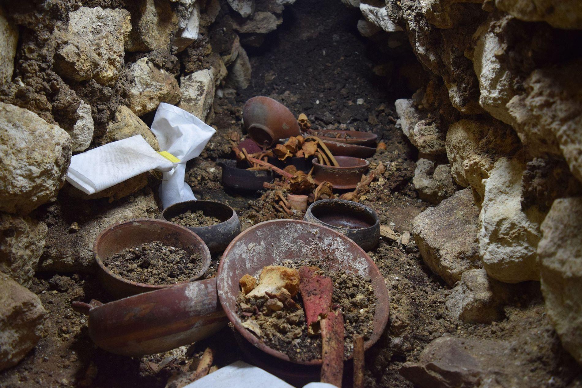"""Die Stätte """"Burial 80"""" während der Ausgrabungen. Im Zentrum befindet sich ein weißes Steingefäß, das von Knochen umgeben ist, die Jahrhunderte nach der Bestattung rot angemalt wurden."""