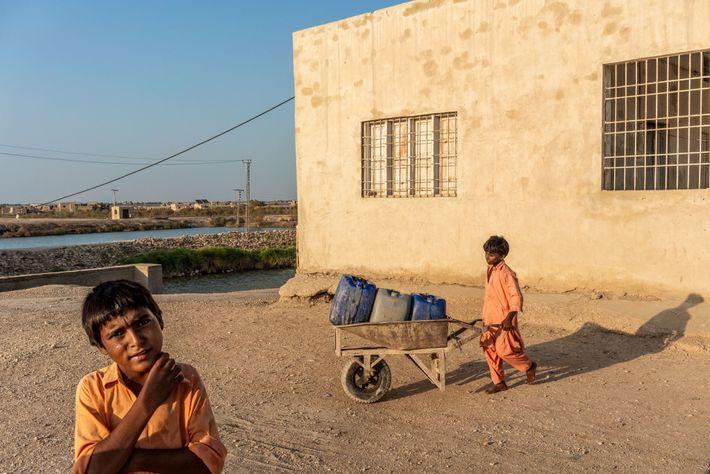 Kinder holen Trinkwasser aus einer Filteranlage am Manchar-See