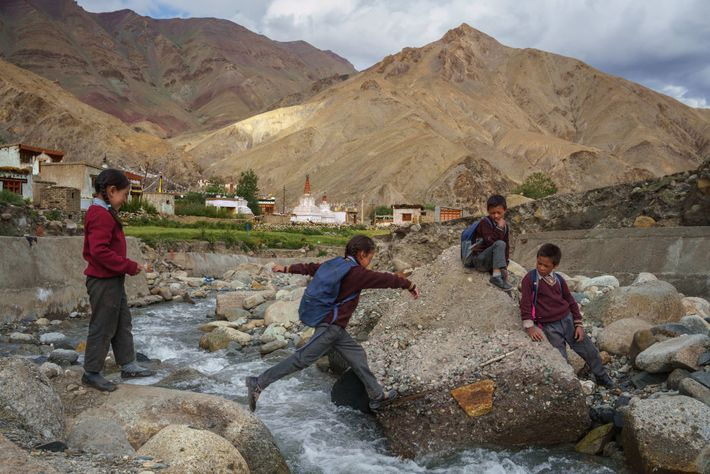 Indische Schulkinder überqueren einen Gletscherbach