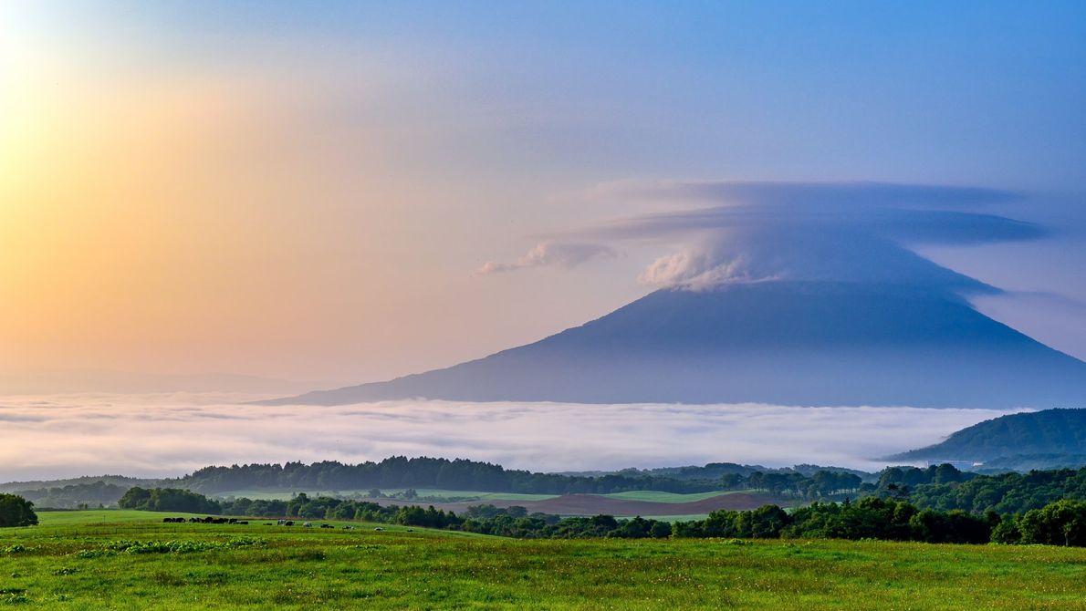 Der Gipfel des Yōtei auf Hokkaido ist von Wolken verhangen, während Nebel um seinen Fuß wabert. ...