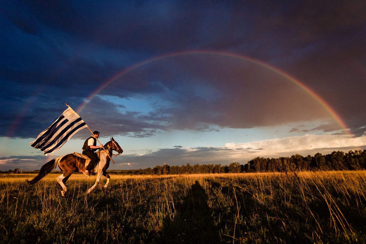In Uruguay galoppiert ein Reiter unter einem Doppelregenbogen entlang, während er die blauweiße Landesfahne in der ...