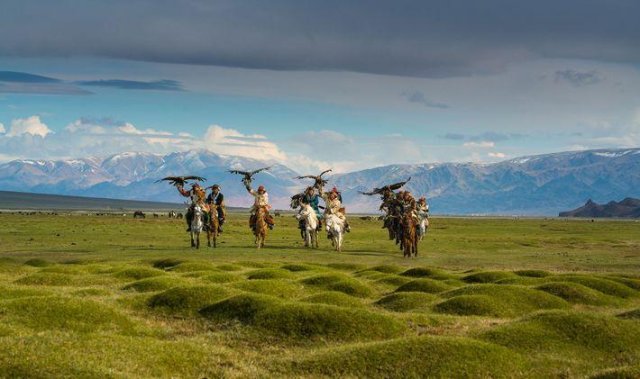 Adlerjäger auf einer grasbewachsenen Ebene in der Mongolei