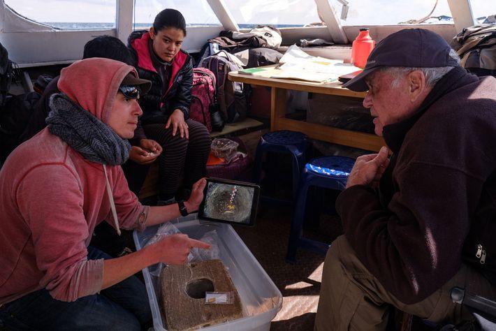An Bord eines Forschungsschiffes auf dem Titicacasee zeigen der Projektleiter Christophe Delaere und andere Teammitglieder ihre ...